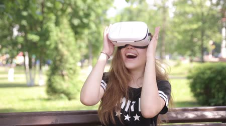 realidade : Handsome girl looking in virtual reality goggles sitting in park, outdoors.