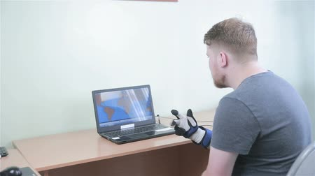 simülasyon : Electronic robotic cyber glove. Man plays VR game operating with 3D bionic simulator glove.