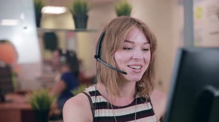 kantoor : Frendly vrouw praten over de headset in een kantoor, call center. Stockvideo