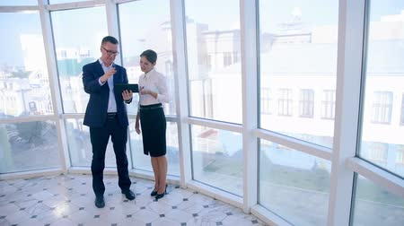discutir : Business, architecture and office concept. Two successful businessmen discuss project on tablet in clean bright office near panoramic window.