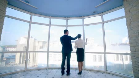 razem : Businessmen man and woman discuss work project in a modern office building near clean panoramic window. Business concept. Steadicam shoot. Wideo