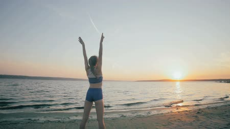 Young girl with a slender figure is engaged in gymnastics at sea at sunrise. Unrecognizable silhouette. 影像素材