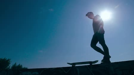 patim : Epic Silhouette of skater riding on skateboard. Sunset sky on a background. Slow motion, steadicam shoot.