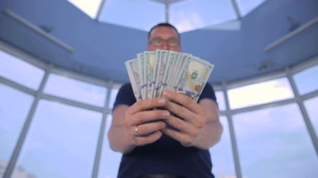 wasted : Confident man showing money, US dollars into camera. Stock Footage