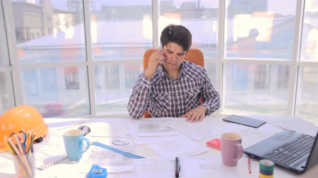 planos : Young busy businessman working with drawings, blueprints in a light, modern office. Stock Footage