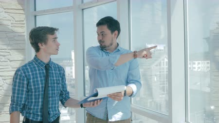 cooperative work : Director discuss project with employee in new modern office. Stock Footage