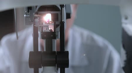 eyepieces : A medical ophthalmological device for checking of eyesight. Unrecognizable doctor working with patient eye testing. Stock Footage