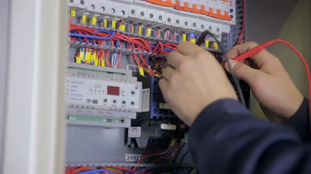 energetyka : Electrician testing electrical power. Industrial factory electrician testing voltage using multimeter at the electrical shield.