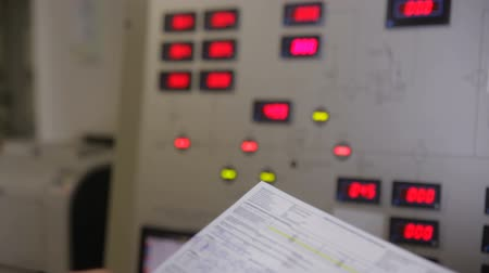 físico : Electrical engineer checking parameters at a control panel of a nuclear plant, writing values into chart. Slider shot. Vídeos