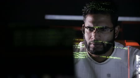 хакер : Male arabic hacker hacks computer in dark. Computer code reflecting on his face. Стоковые видеозаписи