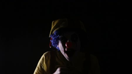тревожный : Scary shot of a spooky mad clown making frightening faces in dark room under stroboscope. Portrait. Стоковые видеозаписи