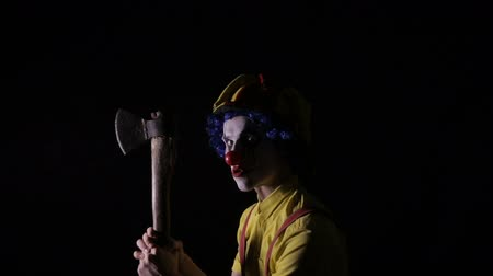slayer : Scary clown with an axe in a dark room. Frightening jester, clown, buffoon. Stock Footage