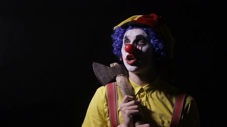 palhaço : Scary clown with an axe in a dark room. Frightening jester, clown, buffoon. Vídeos