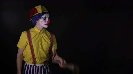 slayer : Scary juggler clown juggling axe in a dark room. Frightening jester, clown, buffoon. Stock Footage