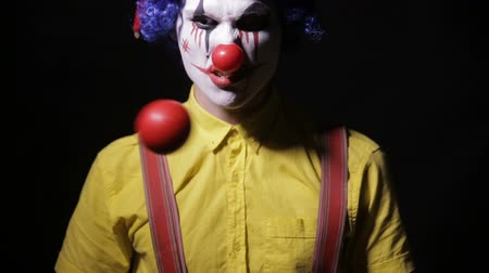 тревожный : Scary mad Juggler clown using juggling pins. Terrible horror clown.