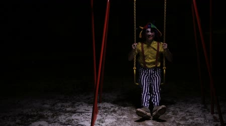 palhaço : Creepy clown in the street, swinging. Nightmare picture.