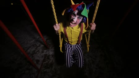 frightful : Creepy clown in the street, swinging. Nightmare picture.