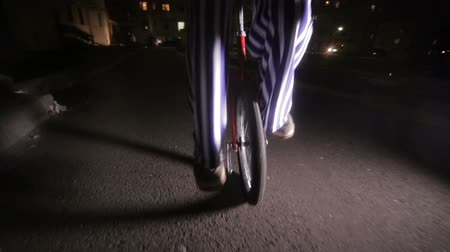 hamis : Sad scary clown riding on unicycles in a dark street.