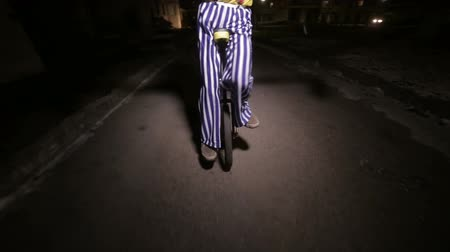 palhaço : Sad scary clown riding on unicycles in a dark street.