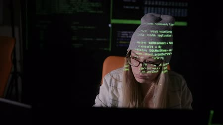 scammer : Female hacker working at the computer in dark at night. Binary code projection on her face. Slider shoot. Front view.