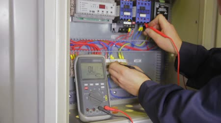 disjuntor : Electric Breaker Box. Electrician testing and switching fuse, breaker in a fuse box.