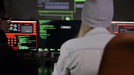 кража : Young man and woman hackers trying to gain access to a computer system.
