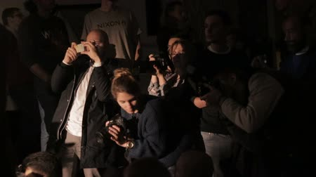 photojournalist : Moscow, Russia - 15 October 2016: Photographers, videographers seminar. Group of photographers and videographers shooting model in the dark.