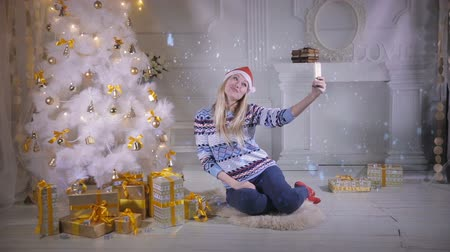 festa : Young pretty woman near Christmas tree making selfie during Christmas Eve. New year selfie Photo. Stock Footage