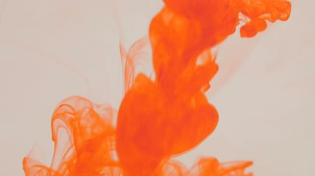 damla : Orange ink in water. On a white background.