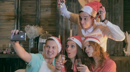 комедия : Young men and women taking self photograph at Christmas party. Cheerful friends making selfie. Slow motion.
