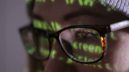 scammer : Female hacker working at the computer in dark at night. Binary code projection on her face. Stock Footage