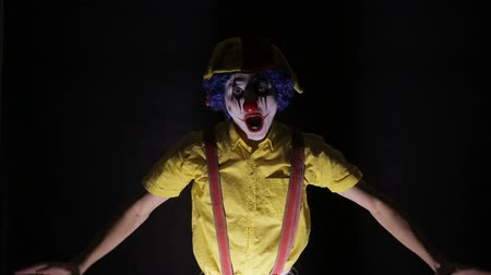 gruesome : Evil, horror clown coming from dark looking into camera.