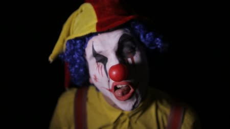 palhaço : The scary clown making horror faces into camera. Halloween horror clowns.