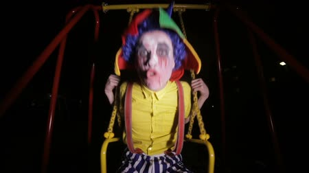 palhaço : Creepy clown swinging at night street. Nightmare picture. Vídeos
