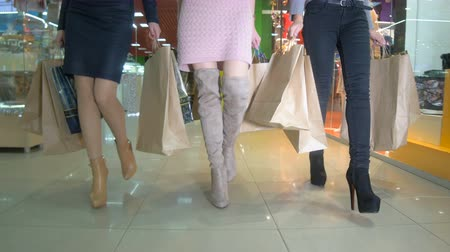nogi : Legs of shopaholics with shopping bags walking in a mall.