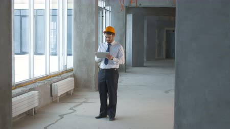 müteahhit : Construction engineer, businessman, realtor inside a new building inspecting construction site using tablet. Stok Video