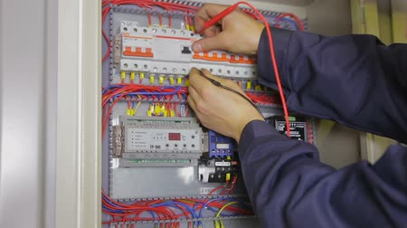 elektryk : electrician hands checking circuit breakers in electrical fuse box.