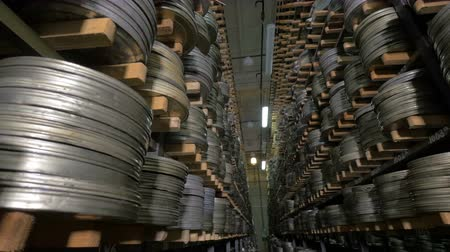 raflar : Old vintage film reel, film tapes in cases lying on archive shelfs. Dolly shot. Stok Video