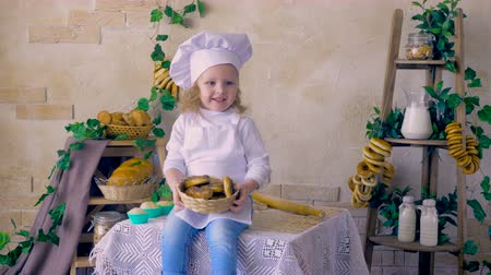 disobedient : Little girl cook throws muffins, sitting in the kitchen.
