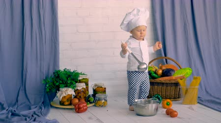 recipient : Little boy sitting in kitchen decoration and cooking with vegetable.