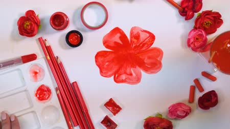 romênia : Female artist hands drawing red flower. Creative artist desk from above. Stock Footage