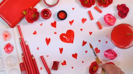 valentin nap : Red palette. Many hearts drawn on a paper. Artist desk from above. Valentines or Mothers Day concept. Stock mozgókép