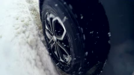 deslizamento : Snow flies into camera. Tire slipping and sliding on snow. On board camera. Close up.