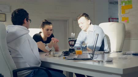 criatividade : Creative engineers team testing innovative robotic technology - bionic arm at a bright modern office.