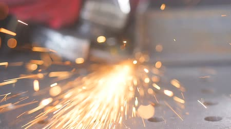 into focus : SLOW MOTION. Sparks is thrown from an angle grinder flies in to the camera. Grinder circle - close-up.