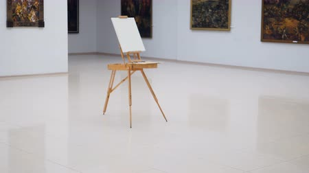 galeria : The steadicam shooting of the easel with white canvas on it. It is standing in the center of the gallery. 4K. Stock Footage