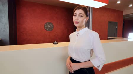 отель : Friendly smiling hotel receptionist greeting hotel guest.
