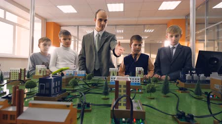 stimulating : Children studying a small model of a city. Stock Footage