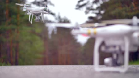 imagem digital gerada : Two quadcopters on the asphalt road, one is taking off. Forest background. 4K.