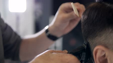 modern manhood : Close-up. Barber performing a haircut technique on a man. Super slow motion. Stock Footage